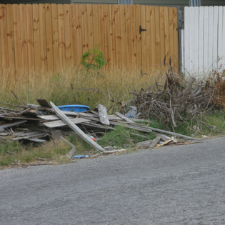 Lumber, trash, and overgrown weeds covering curb