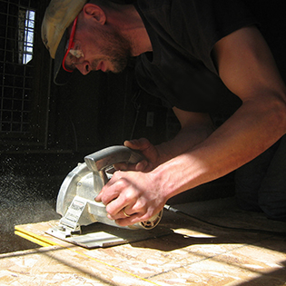 Man Cutting Plywood with a Circular Saw