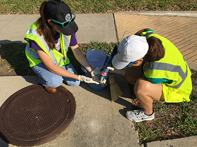 Two women gluing storm inlet marker into the sidewalk.